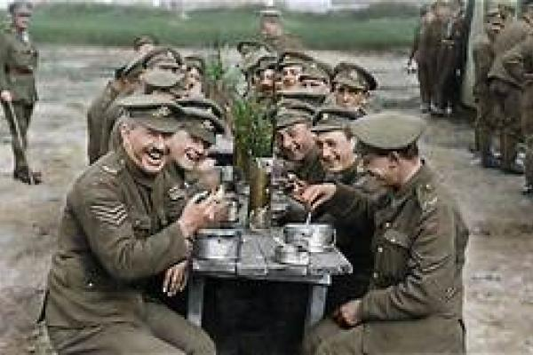 Soldiers from the era of the First World War sit together at a table